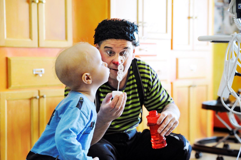 Litet barn blåser såpbubblor med clown